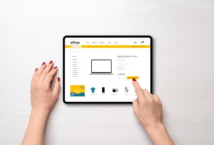 Frau klickt auf Tablet in einem e-Shop auf kaufen