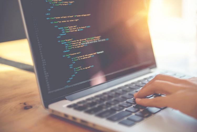 Hand tippt an Laptop, der Code zeigt