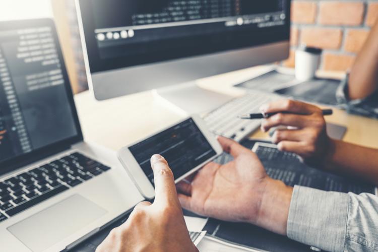 Entwickler halten Handy und sitzen vor Laptop und Rechner