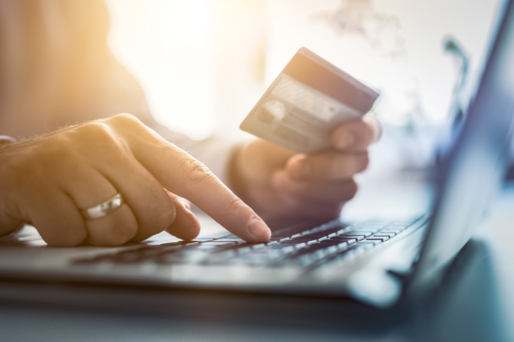 Person tippt auf einem Laptop mit Bankkarte in der anderen Hand