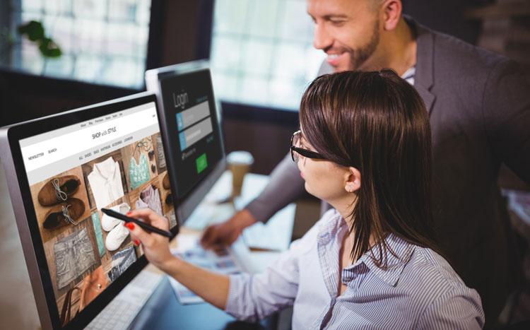 Frau zeigt auf einen Onlineshop am Monitor, Mann guckt über ihre Schulter