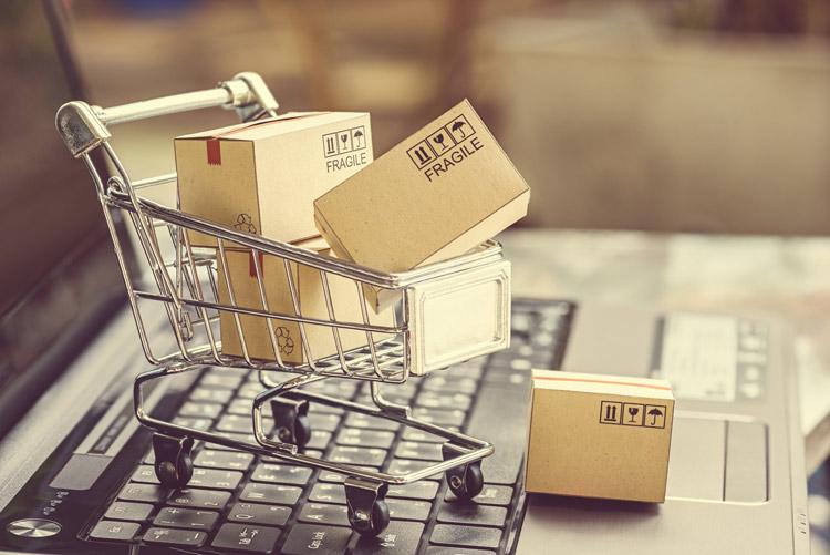 Kleiner Einkaufswagen mit Paketen gefüllt steht auf einem Laptop