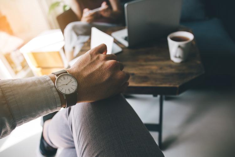 Mann schaut auf Uhr, Laptop im Hintergrund