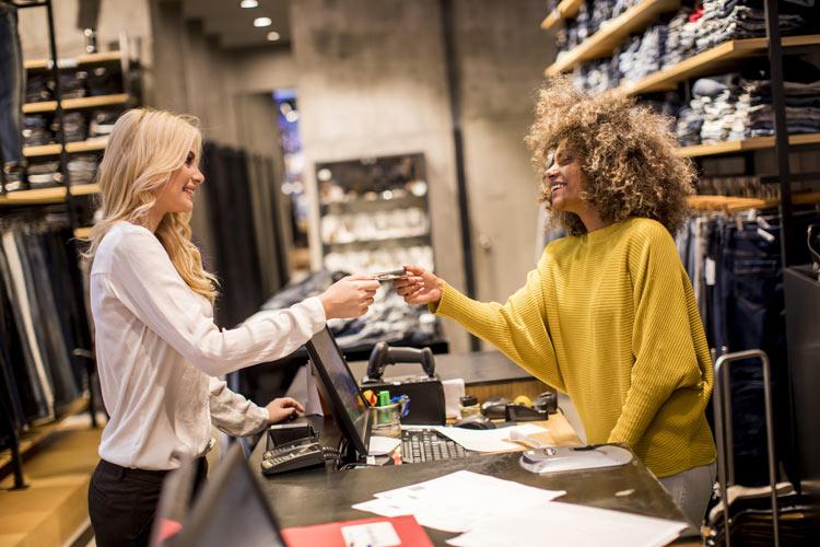 Frau überreicht Kassiererin Geld in einem Modegeschäft