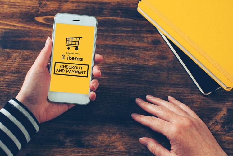 Frau hält Handy, das einen Online-Warenkorb zeigt